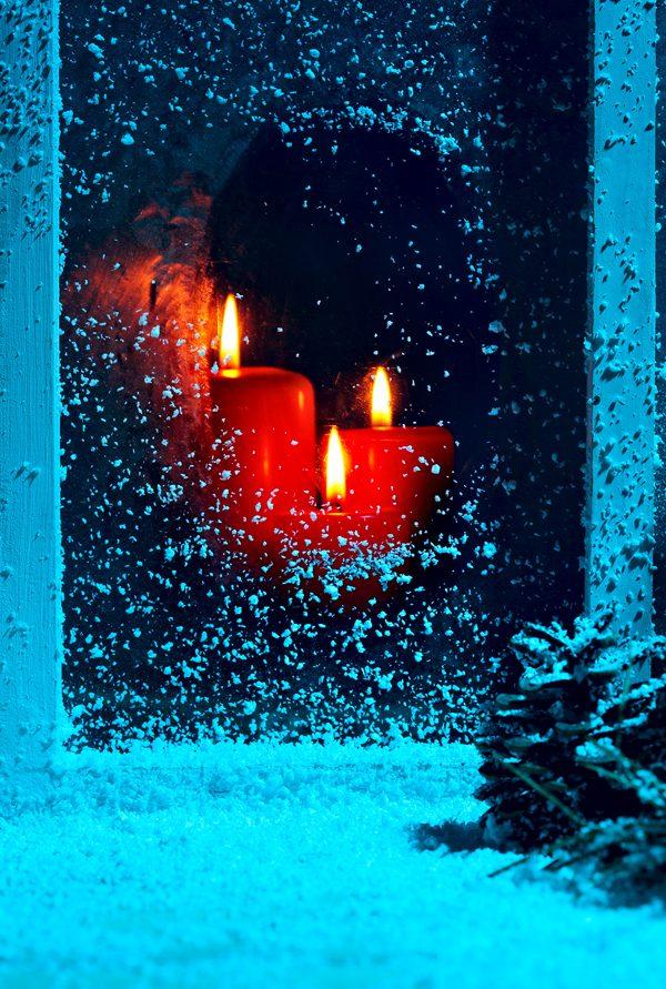 Christmas night! Frozen window burning candles